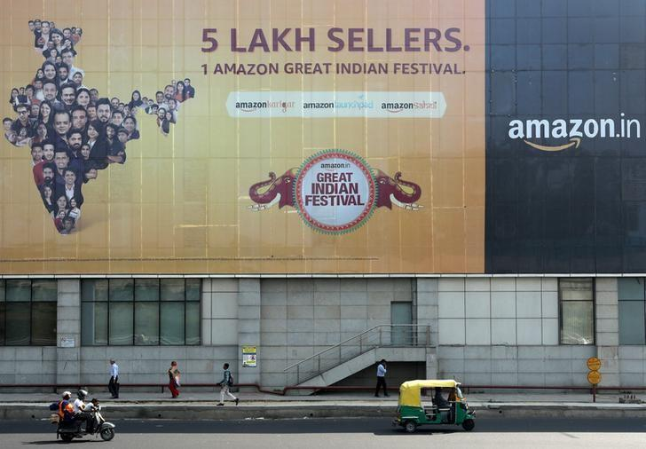 FILE PHOTO: People move past a hoarding of Amazon India outside a metro rail station in New Delhi,