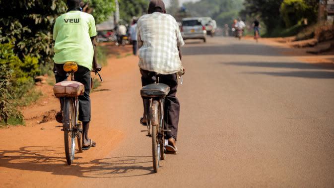 Dua orang warga menaiki sepeda di sebuah ruas jalan di Kampala, ibu kota Uganda (30/6/2020). Warga Uganda kini beralih menggunakan sepeda sebagai sarana transportasi yang mendukung di tengah pandemi COVID-19. (Xinhua/Hajarah Nalwadda)
