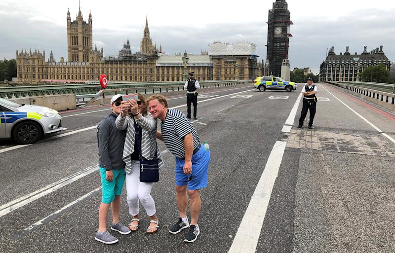 Tourists pose for selfies on Westminster Bridge after a London car attack.