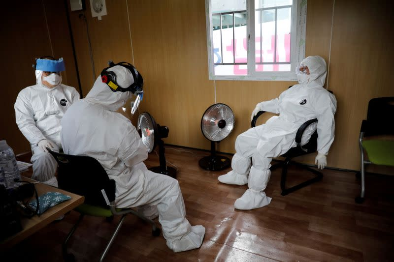 FILE PHOTO: Medical staff in protective gear take a break at a facility of a 'drive-thru' testing center for the novel coronavirus disease of COVID-19 in Yeungnam University Medical Center in Daegu