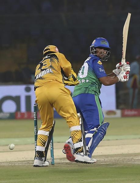 Zeeshan Ashraf of Multan Sultans who scores 50 off 35 balls, hits a boundary as Peshawar Zalimi's Kamran Akmal looks on during the Pakistan Super League match at the National Stadium in Karachi, Pakistan, Friday, March 13, 2020. (AP Photo/Fareed Khan)