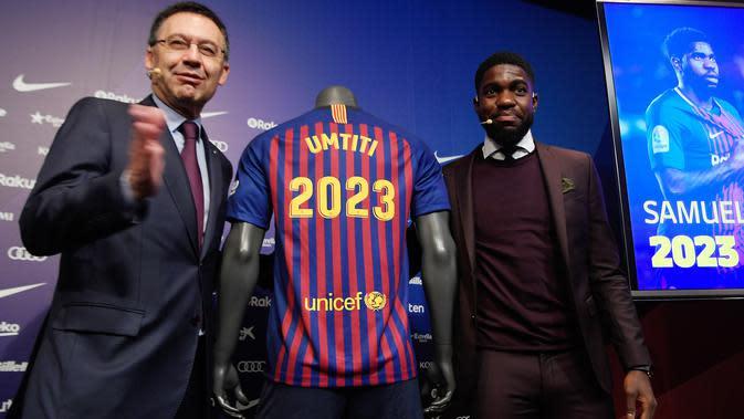 Bek Prancis, Samuel Umtiti dan Presiden Barcelona Josep Maria berpose di samping jersey Barcelona pada pengumuman perpanjangan kontraknya di stadion Camp Nou, Senin (4/6). Umtiti memperpanjang kontraknya bersama Barcelona hingga 2022. (LLUIS GENE/AFP)
