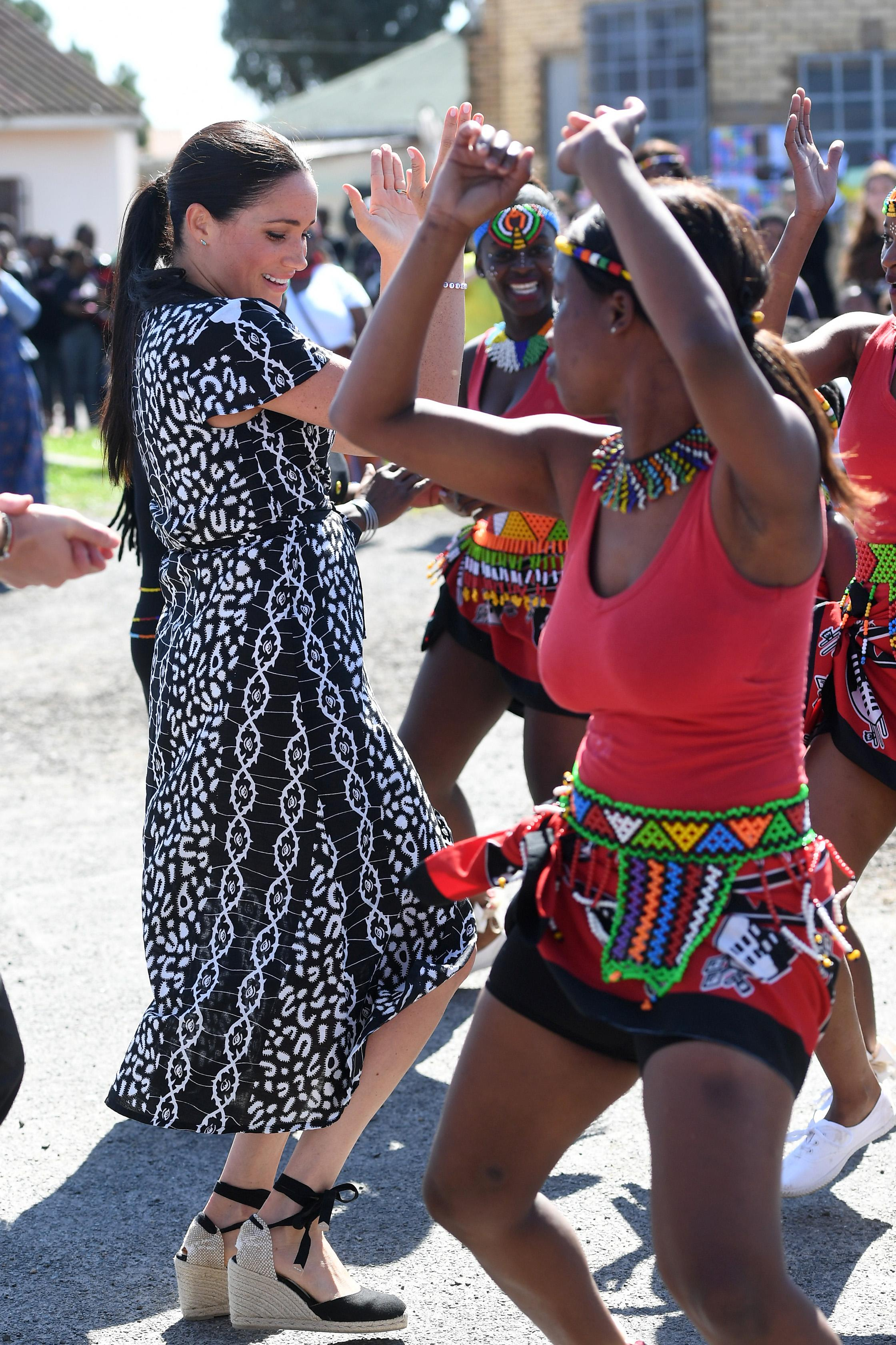 Meghan dances with a local while dancing in Cape Town. [Photo: Getty]
