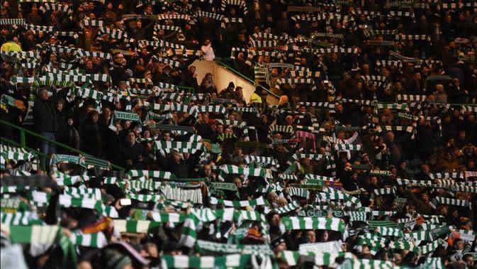 Aksi suporter Celtic saat menjamu Barcelona pada laga kelima Grup C Liga Champions di Celtic Park, Rabu (23/11/2016). (AFP/Paul Ellis)