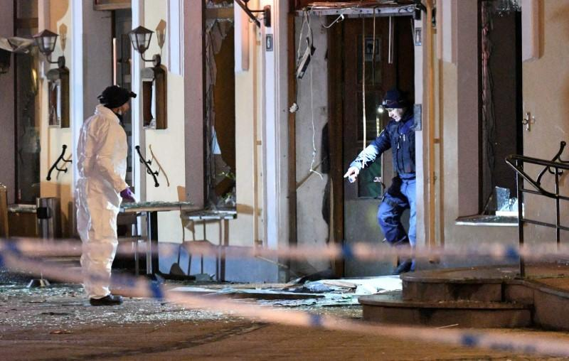 FILE PHOTO: Police officers investigate the site of an explosion at the entrance of a nightclub in Malmo