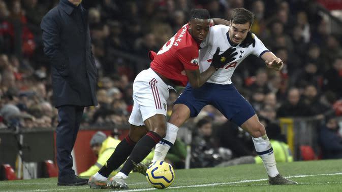 Bek Manchester United, berusaha melewati pemain Tottenham Hotspur, Harry Winks pada pertandingan lanjutan Liga Inggris di Old Trafford, Rabu (4/12/2019). MU menang tipis atas Tottenham 2-1. (AP Photo/Rui Vieira)