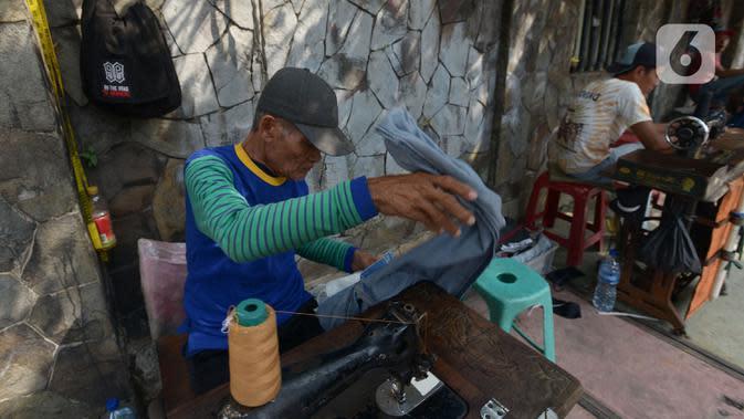 Sutayono menyelesaikan jahitan pelanggan di kawasan Matraman, Jakarta, Jumat (24/7/2020). Pria 74 tahun itu rencananya berangkat haji pada 2022 mendatang usai melunasi administrasi sejak 2016 silam dari hasil menjahit, namun keberangkatannya harus diundur akibat Covid-19. (merdeka.com Imam Buhori)