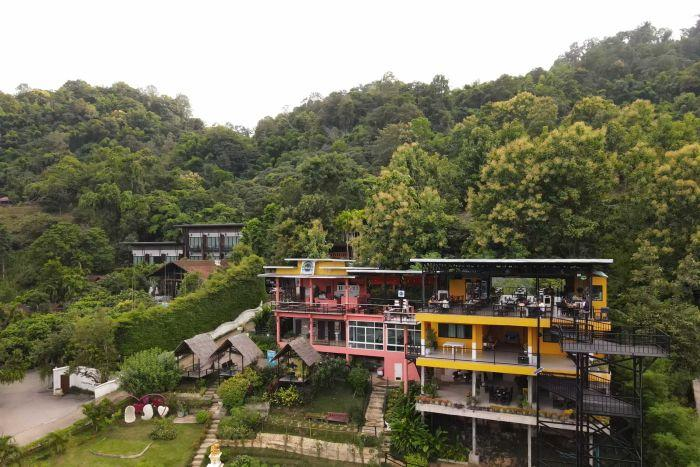 A colourful restaurant nestled into a background of green trees with little huts sitting out front.
