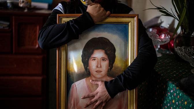Liset Diaz, 35, dari Peru memegang lukisan neneknya Edita Leiva -di masa mudanya-, 76, yang meninggal karena COVID-19 di rumahnya di Chorrillos, selatan Lima, Peru, 11 Agustus 2020. Sepertiga dari kematian global akibat COVID-19 terjadi di Amerika Latin. (ERNESTO BENAVIDES/AFP)