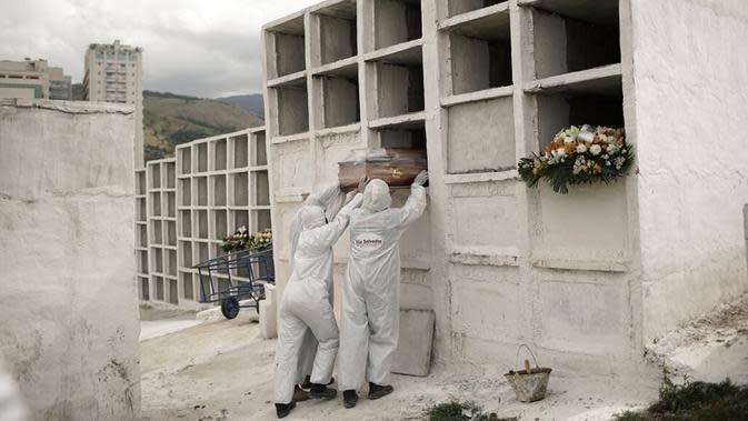 Petugas pemakaman menempatkan peti mati berisi jenazah pasien COVID-19 Jose de Arimateia, 65, ke dalam makam di Nova Iguacu, Brasil, 24 September 2020. Menurut perhitungan Reuters pada September, rata-rata lebih dari 5.400 warga dunia meninggal setiap 24 jam. (AP Photo/Silvia Izquierdo, File)