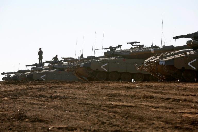 Israeli tanks stand guard close to the armistice line with Syria on the strategic Golan Heights