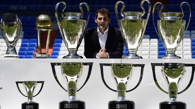 Iker Casillas berpose dengan trofi juara yang pernah diraihnya bersama Real Madrid saat setelah menyampaikan salam perpisahan di Stadion Santiago Bernabeu, Madrid. (13/7/2015). (AFP/Javier Soriano)