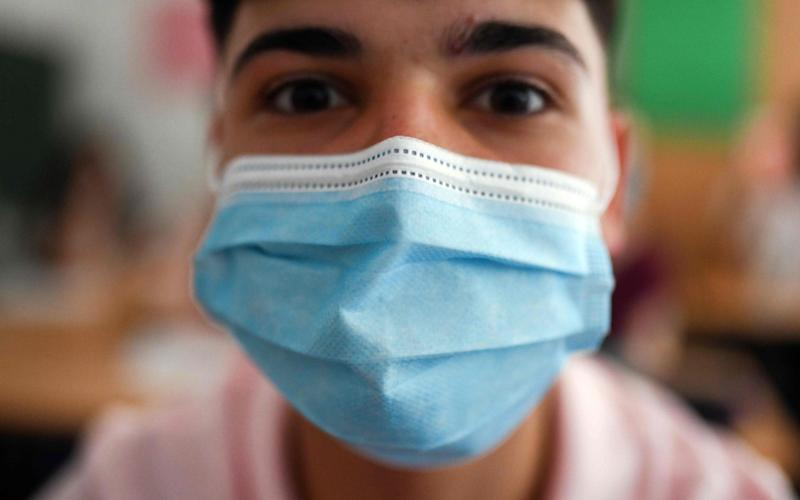 Three fold masks stop about 90 per cent of the virus emitted from an infected individual - Ina Fassbender/AFP