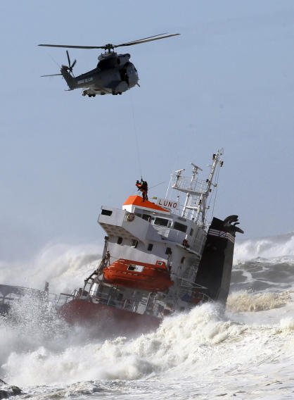 A sailor is helped lifted off by a military helipcopter after a Spanish cargo ship that slammed into a jetty in choppy Atlantic Ocean waters off Anglet, southwestern France, Wednesday, Feb. 5, 2014. The hold of the ship, the Luno, was empty when the accident occurred along the coast of the town of Anglet, and a small amount of fuel was spilling into the water, officials said. The ship had been heading to a nearby port to load up with cargo when its engine conked out and the rough waves carried it into the jetty. (AP Photo/Bob Edme)
