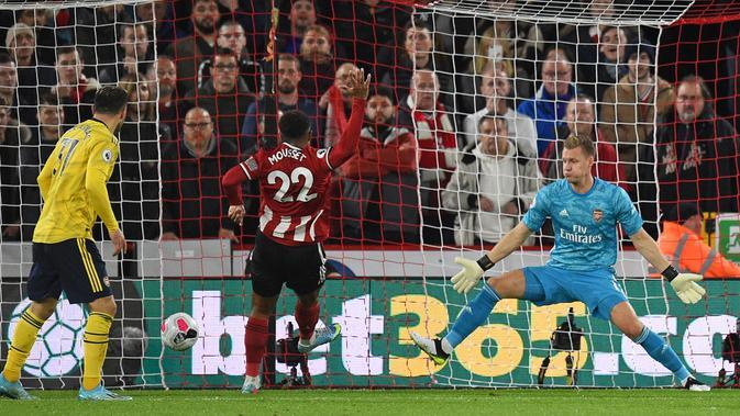 Striker Sheffield United Lys Mousset (tengah) mencetak gol ke gawang Arsenal yang dijaga kiper Jerman Bernd Leno (kanan) pada pertandingan Liga Inggris di Bramall Lane, Sheffield, Inggris, Senin (21/10/2019). Sheffield United menang1-0. (Oli SCARFF/AFP)