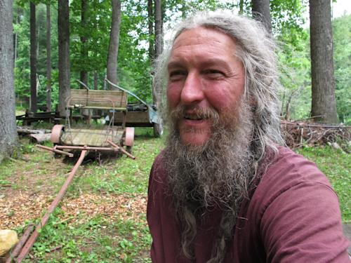 Eustace Conway sits near horse-drawn farm implements at his Turtle Island Preserve in Triplett, N.C., on Thursday, June 27, 2013. People come from all over the world to learn natural living and how to go off-grid, but local officials ordered the place closed over health and safety concerns. (AP Photo/Allen Breed)
