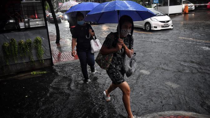 Orang-orang berjalan di jalan yang banjir saat hujan deras di Bangkok (23/9/2020). (AFP/Mladen Antonov)