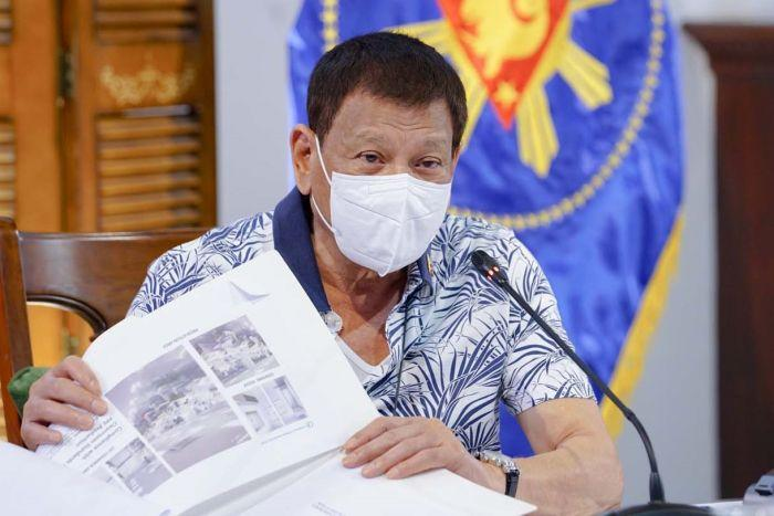 Philippines President Rodrigo Duterte holds documents and wears a mask.