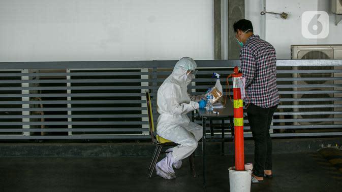 Petugas Hotel Ibis Styles Mangga Dua Square Jakarta memakai alat pelindung diri (APD) lengkap menerima barang kiriman untuk pasien Covid-19 berstatus orang tanpa gejala (OTG) yang sedang melakukan isolasi mandiri, Kamis (1/10/2020). (Liputan6.com/Faizal Fanani)