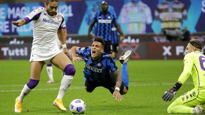 Pemain Inter Milan Lautaro Martinez (tengah) jatuh saat berebut bola dengan pemain Fiorentina Martin Caceres pada pertandingan Serie A di Stadion San Siro, Milan, Italia, Sabtu (26/9/2020). Inter Milan mengalahkan Fiorentina dengan skor 4-3. (AP Photo/Luca Bruno)