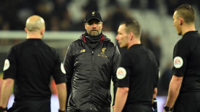 Pelatih Liverpool, Jurgen Klopp berjalan menghampiri para wasit usai pertandingan melawan West Ham United pada lanjutan Liga Inggris di The London Stadium (4/2). Liverpool bermain imbang 1-1 atas West Ham. (AFP Photo/Glyn Kirk)