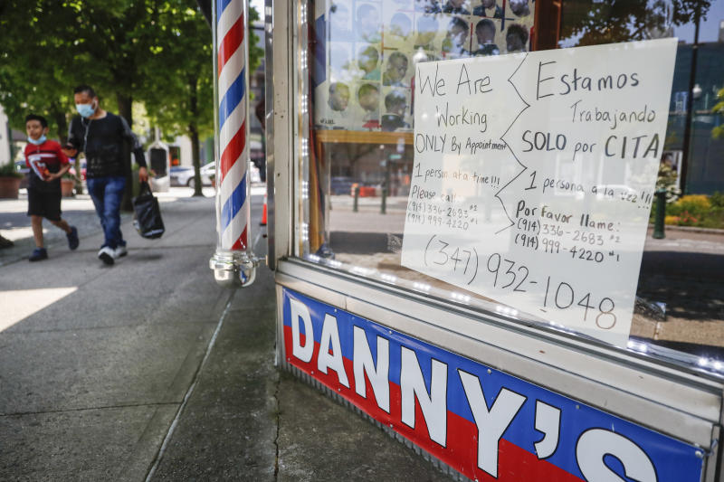 Pedestrians pass a barbershop that displays a sign advertising haircuts by appointment only, Tuesday, May 26, 2020, in New Rochelle, N.Y. (AP Photo/John Minchillo)