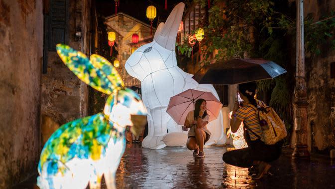 Seorang wanita berfoto di depan instalasi Jade Rabbit di Kwai Chai Hong, Kuala Lumpur, Malaysia, 25 September 2020. Delapan desain unik instalasi seni Jade Rabbit dipamerkan di Kwai Chai Hong dalam sebuah acara untuk merayakan Festival Pertengahan Musim Gugur mendatang. (Xinhua/Zhu Wei)