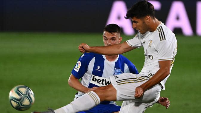 Gelandang Real Madrid, Marco Asensio, berebut bola dengan bek Alaves, Adrian Marin Gomez, pada laga lanjutan La Liga pekan ke-35 di Stadion Alfredo di Stefano, Sabtu (11/7/2020) dini hari WIB. Real Madrid menang 2-0 atas Alaves. (AFP/Gabriel Bouys)