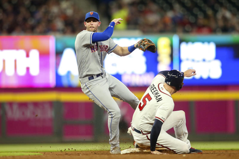 Aug 13, 2019; Atlanta, GA, USA; New York Mets second baseman Jeff McNeil (6) turns a double play over Atlanta Braves first baseman Freddie Freeman (5) in the fourth inning at SunTrust Park. Mandatory Credit: Brett Davis-USA TODAY Sports
