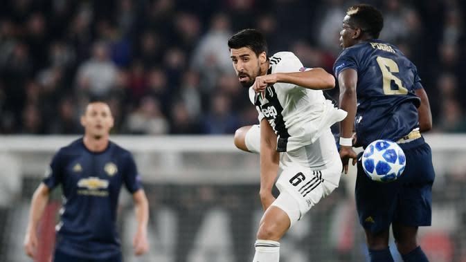 Gelandang Juventus, Sami Khedira, duel udara dengan gelandang Manchester United, Paul Pogba, pada laga Liga Champions di Stadion Allianz, Turin, Rabu (7/11). Juventus kalah 1-2 dari MU. (AFP/Marco Bertorello)