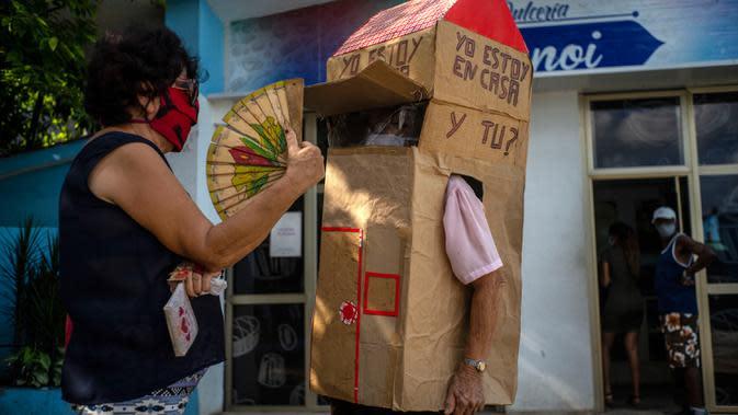 Seorang perempuan berbincang dengan pensiunan perawat bernama Feridia Rojas (82) yang memakai kotak kardus untuk melindungi dirinya dari penyebaran Covid-19 di Havana, Kuba, 8 Juli 2020. Kardus pelindung itu dilengkapi pesan yang ditulis tangan,