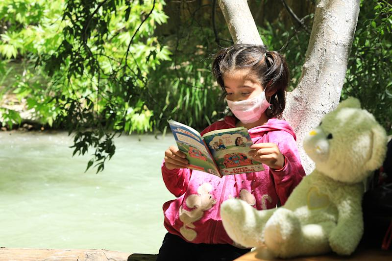 MALATYA, TURKEY - MAY 13: A girl reads a book at the park in Tohma Canyon after children under 14 years across Turkey allowed to leave their homes, remaining within walking distance and wearing masks, on May 13 between 11 a.m. and 3 p.m. local time, in Malatya, Turkey on May 13, 2020. Turkey on Wednesday eased coronavirus (Covid-19) restrictions for young people under 14 years old. (Photo by Ayhan Iscen/Anadolu Agency via Getty Images)