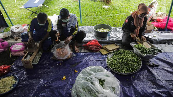Petugas Taruna Siaga Bencana (Tagana) menyiapkan masakan di Dapur Umum Kementerian Sosial Peduli Dampak Covid-19 di Kompleks Gedung Konvensi TMP Nasional-Utama, Kalibata, Jakarta, Rabu (8/4/2020). Dalam sehari, petugas menyiapkan 5.000 hingga 9.000 paket nasi bungkus. (Liputan6.com/Faizal Fanani)