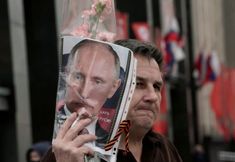 FILE PHOTO: A man demonstrates a portrait of Russian President Vladimir Putin during the celebrations of Victory Day in Moscow