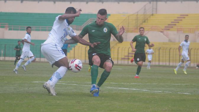 Perebutan bola antara bek PSS Sleman, Aaron Evans (hijau) dengan striker Persib Bandung, Zulham Zamrun dalam laga uji coba di Stadion Sultan Agung, Bantul, Senin (17/2/2020). (Bola.com/Vincentius Atmaja)