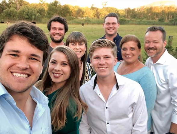 Bindi Irwin and Chandler Powell with Robert and Terri Irwin and Chandler's parents Shannan and Chris Powell pose in the Australian bush in smart casual wear