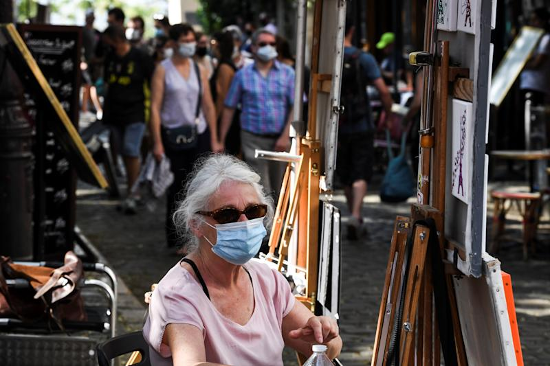 A street artist wearing a protective facemask sits next to her easel at the place du Tertre, in the Montmartre neighbourhood, in Paris, on August 11, 2020 as the mayor decided to make the mask compulsory in certain areas of the city to fight against the rising of new infected cases of COVID-19 (the novel coronavirus). (Photo by ALAIN JOCARD / AFP) (Photo by ALAIN JOCARD/AFP via Getty Images)