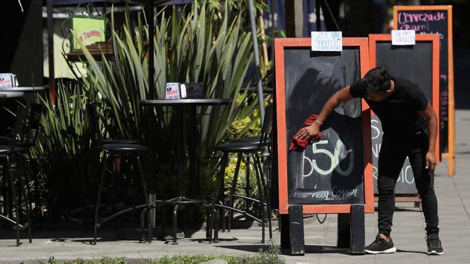 Seorang pelayan menghapus papan pengumuman minuman spesial untuk menggantikannya dengan makanan spesial di bar dan restoran kosong di Mexico City (23/3/2020). (AP Photo/Fernando Llano)