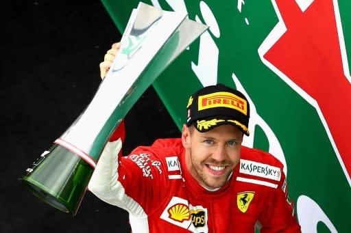 Ferrari's Sebastian Vettel celebrates on the podium with his trophy after winning the Canadian Formula One Grand Prix at Circuit Gilles Villeneuve