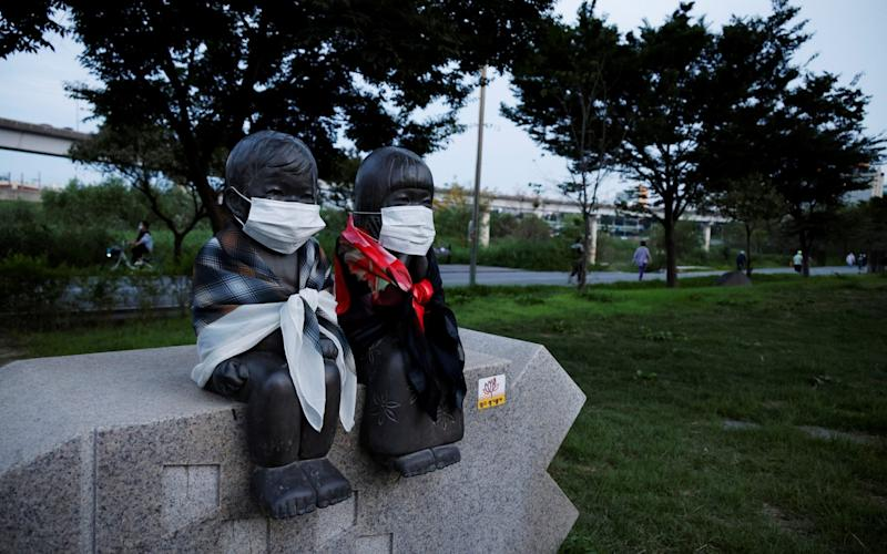 A sculpture of brother and sister is pictured with protective masks on, as people stroll in a park in Seoul - Reuters