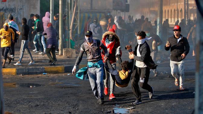 Demonstran antipemerintah yang terluka dibawa untuk menerima pertolongan pertama saat bentrok dengan pasukan keamanan di Najaf, Irak, Kamis (28/11/2019). Kerusuhan di Ibu Kota dan wilayah selatan Irak terus meningkat setelah pembakaran gedung Konsulat Iran. (AP Photo/Anmar Khalil)