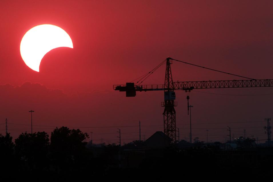 """The moon begins to partially block the sun as the sun sets at 8:02 p.m. silhouetting a crane just west of downtown Houston during a rare solar eclipse known as the """"ring of fire"""" Sunday, May 20, 2012, in Houston. The annular eclipse, in which the moon passes in front of the sun leaving only a golden ring around its edges, was visible to wide areas across China, Japan and elsewhere in the region before moving across the Pacific to be seen in parts of the western United States. (AP Photo/Houston Chronicle, Johnny Hanson)"""