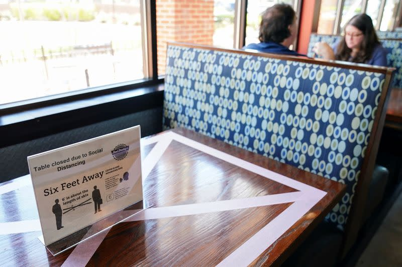 Customers eat lunch next to a table closed for social distancing at Bad Daddy's Burger Bar on the day restaurants and theaters were allowed to reopen to the public as part of the phased reopening of businesses from the coronavirus disease rules in Smyrn