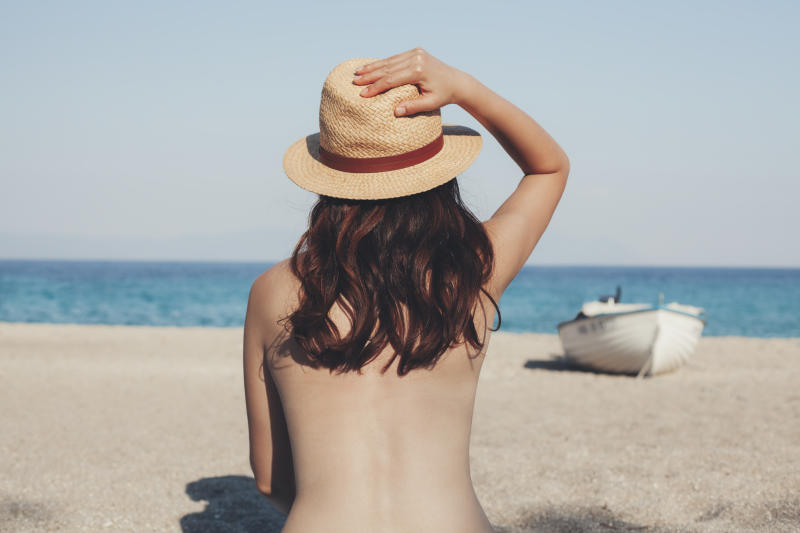 A photo of a young woman on the beach looking at the sea