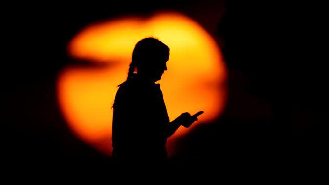 Seorang wanita melihat teleponnya di sebuah taman ketika matahari terbenam di Kansas City, Missouri, Amerika Serikat, Senin (29/6/2020). Matahari terbenam dan matahari terbit lebih cerah dari biasanya belakangan ini karena debu di atmosfer dari awan debu Sahara. (AP Photo/Charlie Riedel)