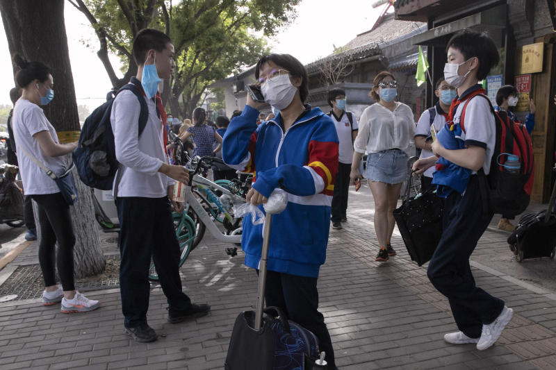 Students wearing masks to curb the spread the new coronavirus leave after the end of a school day in Beijing on Wednesday, June 3, 2020. Students in the Chinese capital have been slowly returning to school as authorities continue to restore normalcy after the shutdown over the coronavirus outbreak. (AP Photo/Ng Han Guan)