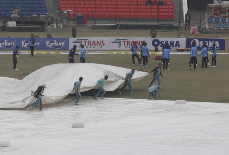 Ground staff cover a pitch during a light rain at Gaddafi stadium, in Lahore, Pakistan, Monday, Jan. 27, 2020. Pakistan and Bangladesh are scheduled to play the last T20 which is delayed due to rain in Lahore. (AP Photo/K.M. Chaudary)