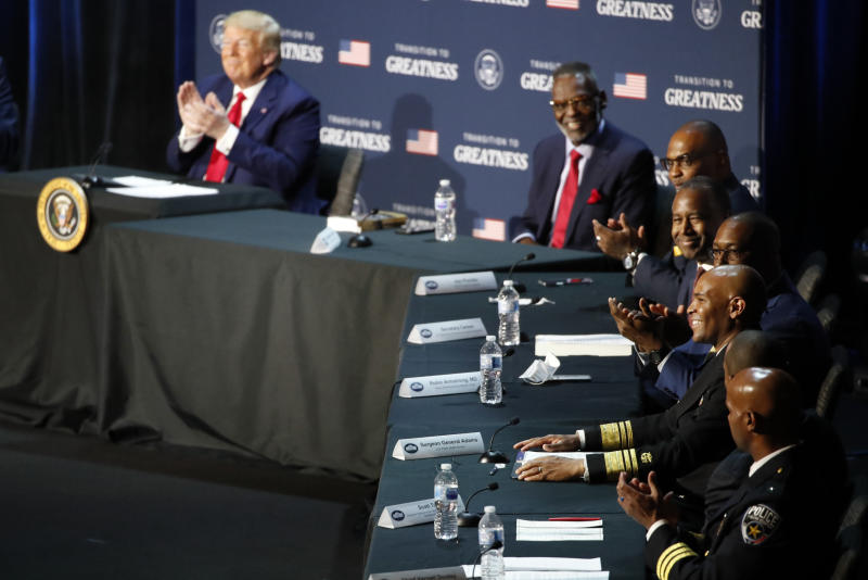 """President Donald Trump applauds as U.S. Surgeon General Jerome Adams speaks during a roundtable discussion about """"Transition to Greatness: Restoring, Rebuilding, and Renewing,"""" at Gateway Church Dallas, Thursday, June 11, 2020, in Dallas.(AP Photo/Alex Brandon)"""