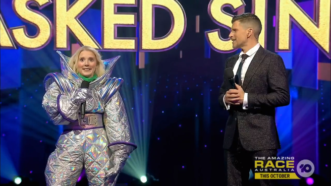 A photo of Nikki Webster in her Masked Singer Alien costume on stage with and Osher Gunsberg..