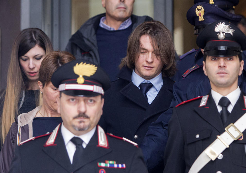 Raffaele Sollecito, center,  leaves Italy's highest court building, in Rome, Friday, March 27, 2015. American Amanda Knox and her Italian ex-boyfriend expect to learn their fate Friday when Italy's highest court hears their appeal of their guilty verdicts in the brutal 2007 murder of Knox's British roommate Meredith Kercher. At left, is  Greta Menegaldo,  the girlfriend of Raffaele Sollecito. (AP Photo/Riccardo De Luca )